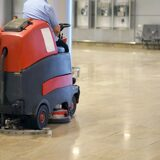Man driving professional floor cleaning machine at airport or railway station or supermarket. Floor care and cleaning service